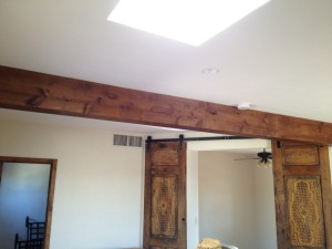 Finished Knotty Alder Beam Box w/reclaimed doors on barn door hardware in the background